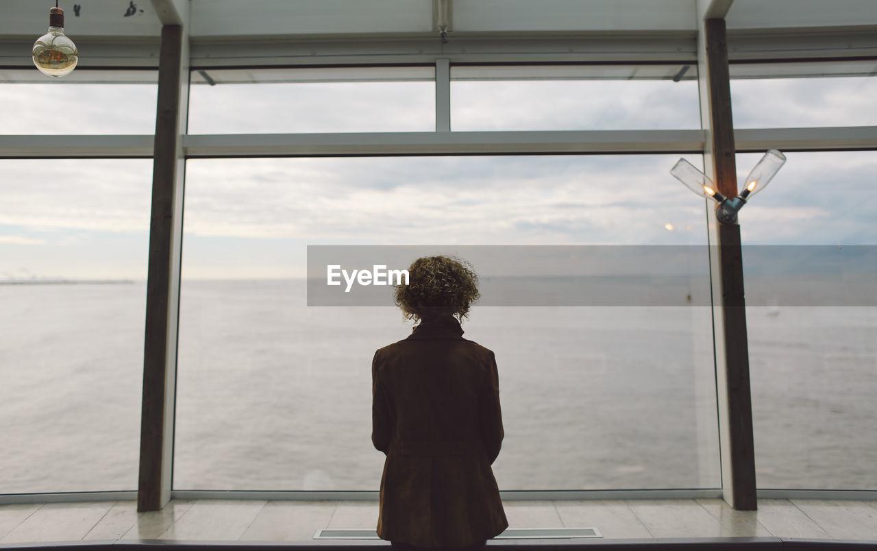 Rear View Of Woman Standing On Scheveningen Pier At Beach During Sunset
