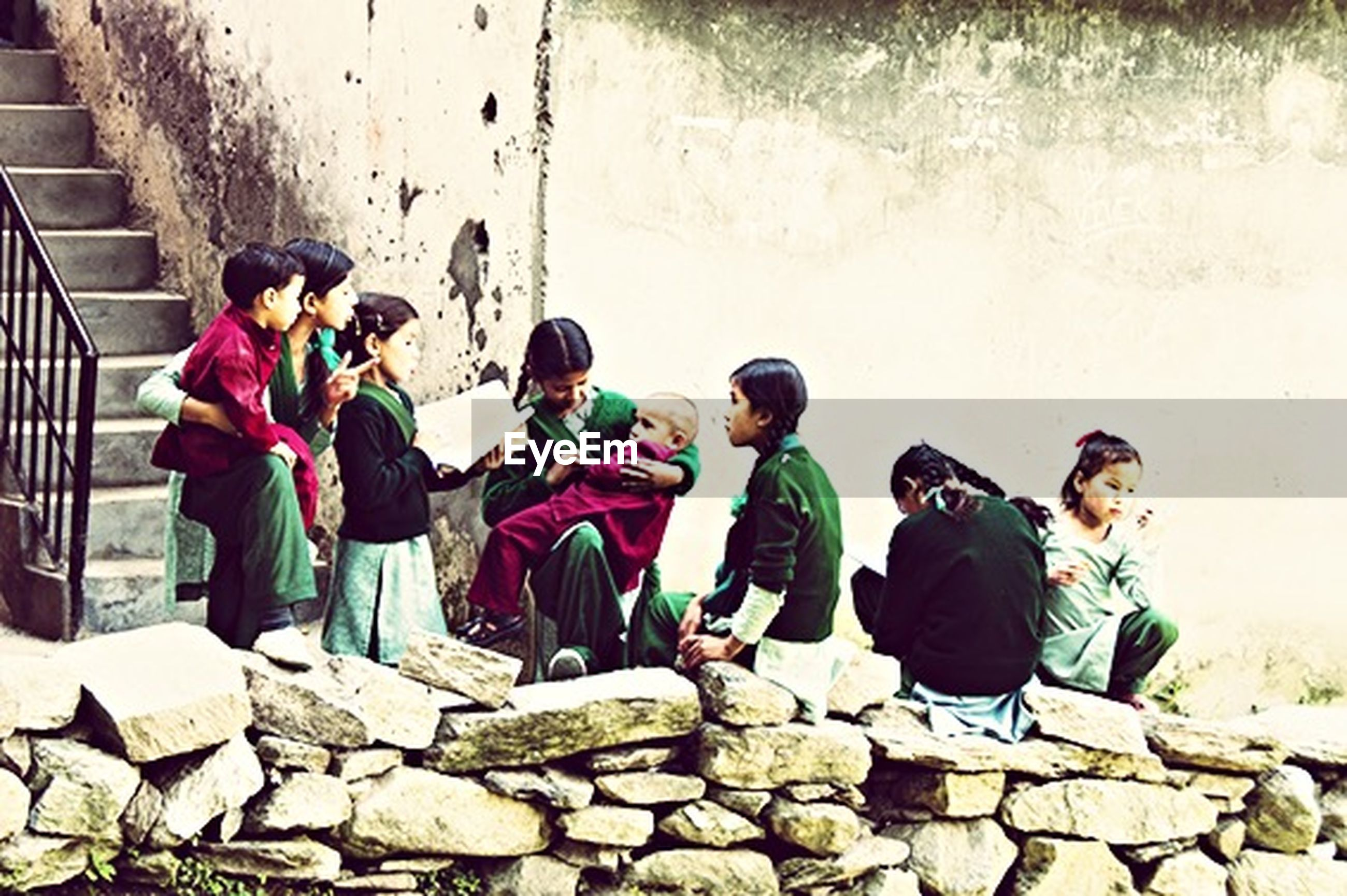 lifestyles, togetherness, leisure activity, men, casual clothing, full length, bonding, boys, friendship, person, love, wall - building feature, sitting, rear view, standing, built structure, day, architecture