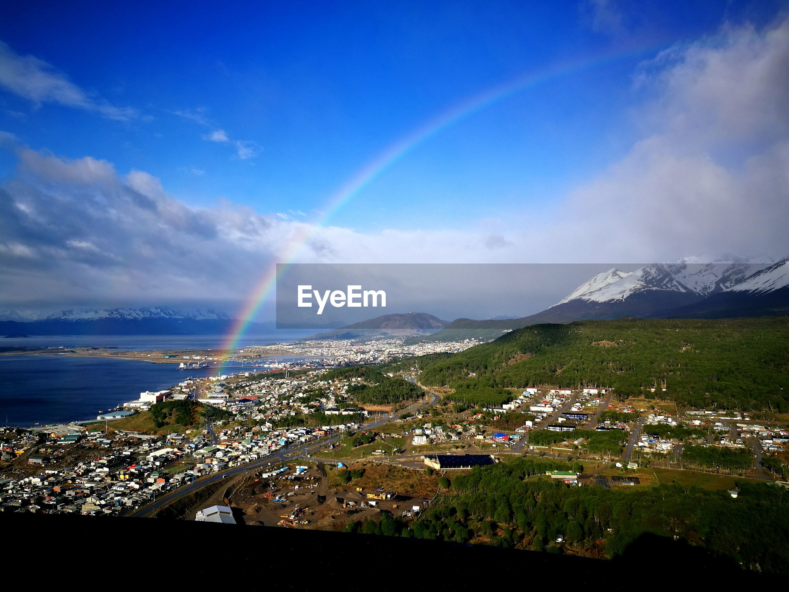SCENIC VIEW OF RAINBOW OVER CITY BY SEA