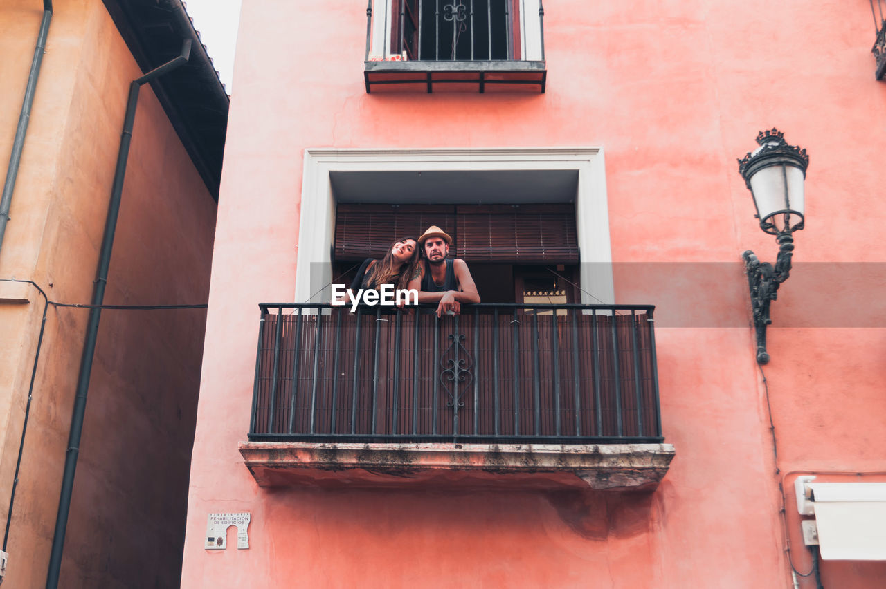 Portrait Of Young Man With Girlfriend Standing At Balcony
