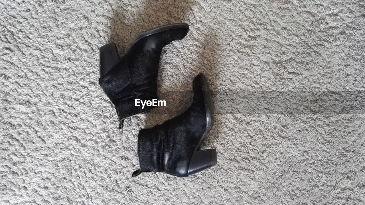 Directly Above Shot Of Black Shoes On Carpet