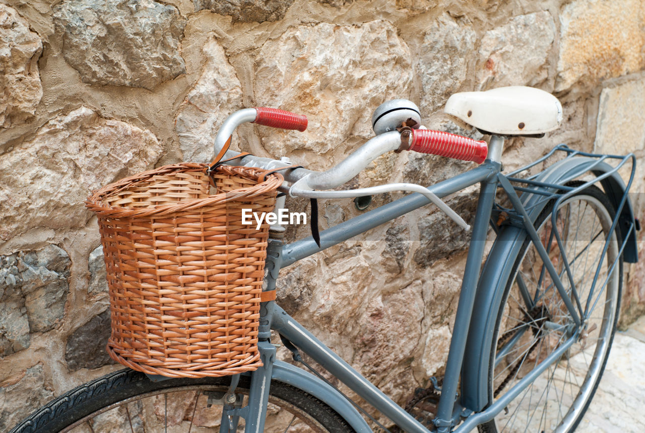 Bicycle with basket parked by wall