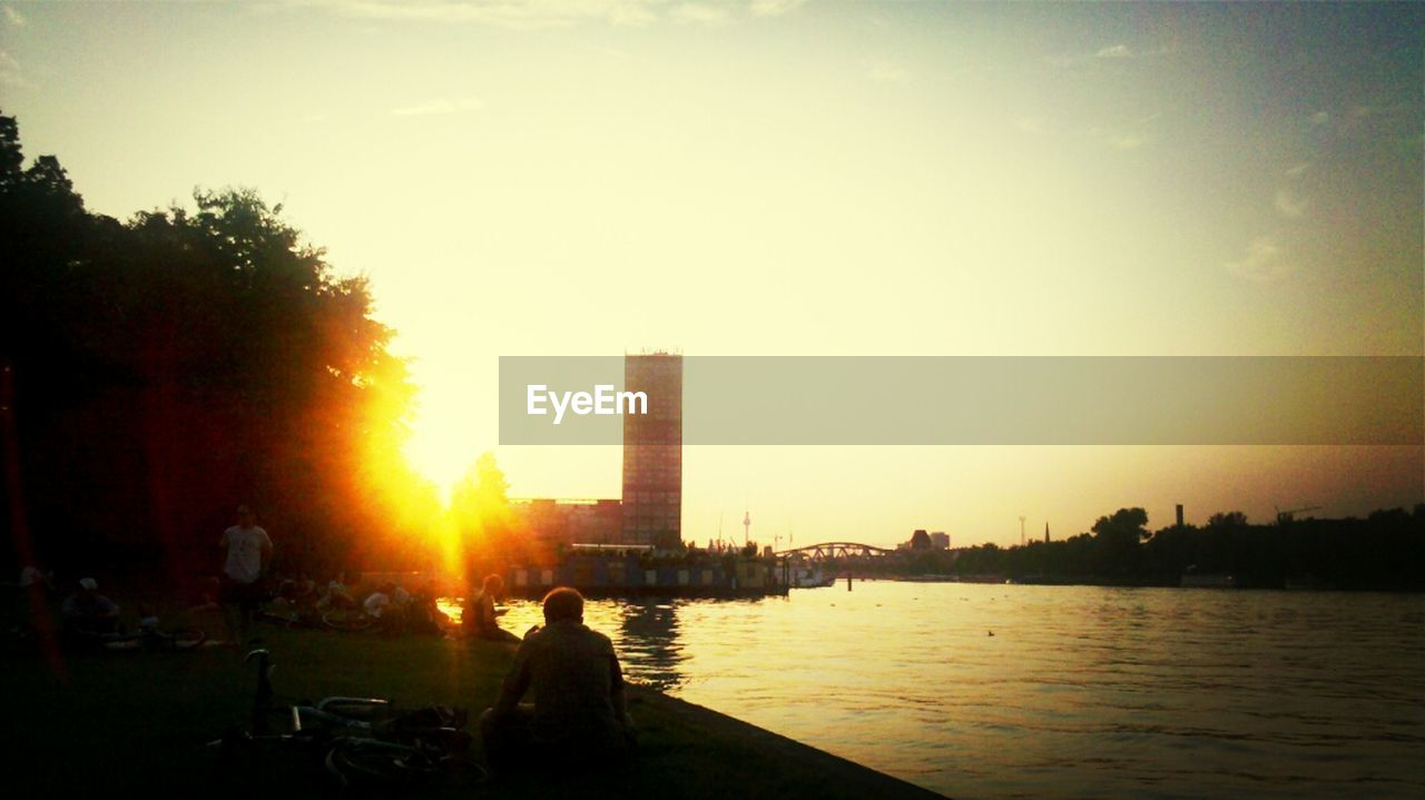 skyscraper, built structure, architecture, building exterior, city, sunset, river, sky, cityscape, modern, outdoors, tree, silhouette, real people, water, urban skyline, nature, day