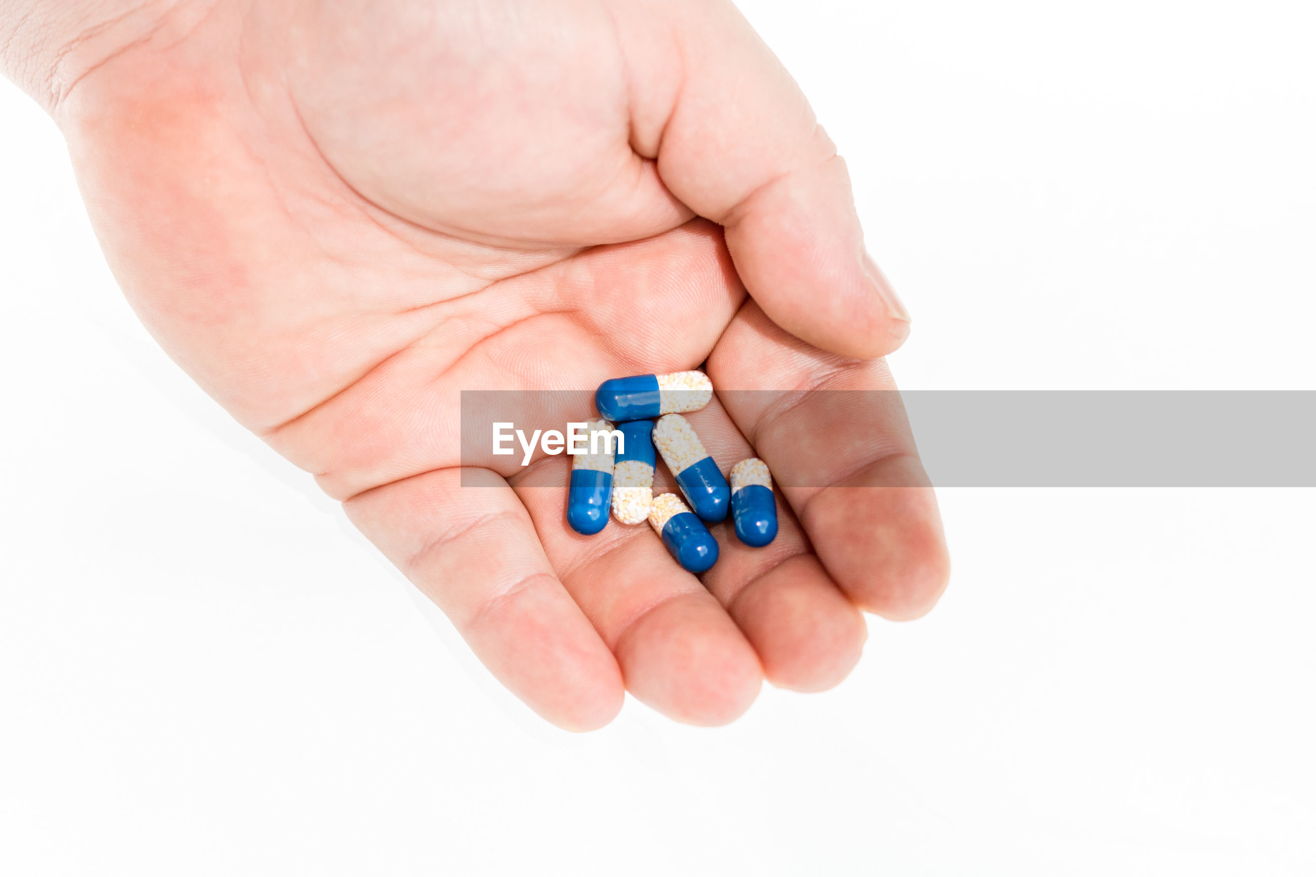 Close-up of hand holding capsules over white background