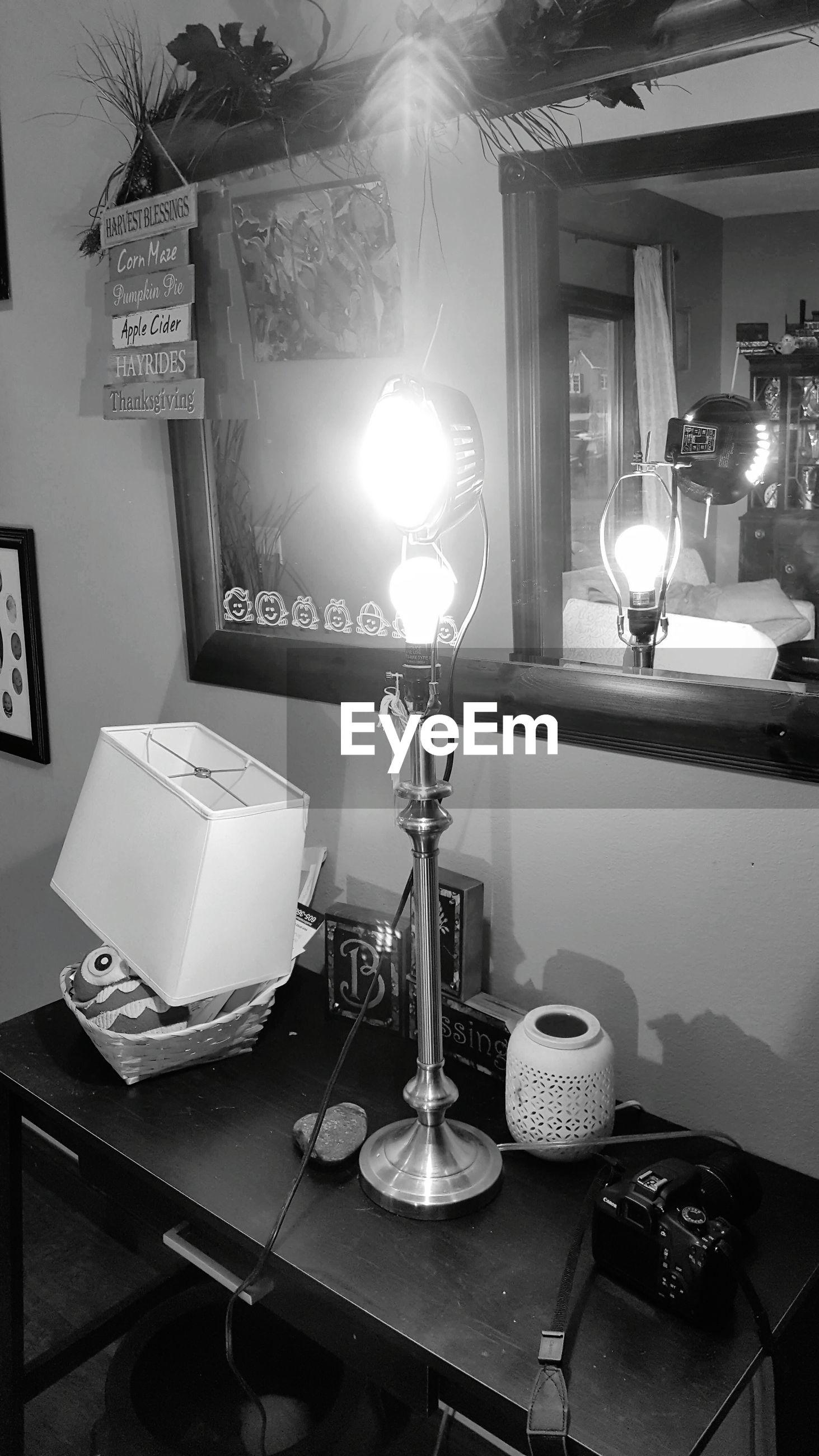 ILLUMINATED LAMP ON TABLE IN RESTAURANT