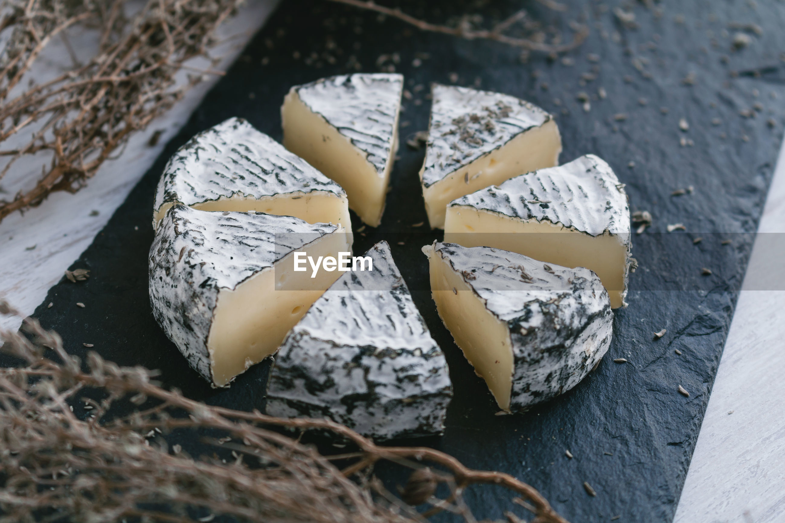 High angle view of cheese slices and herbs on cutting board in kitchen