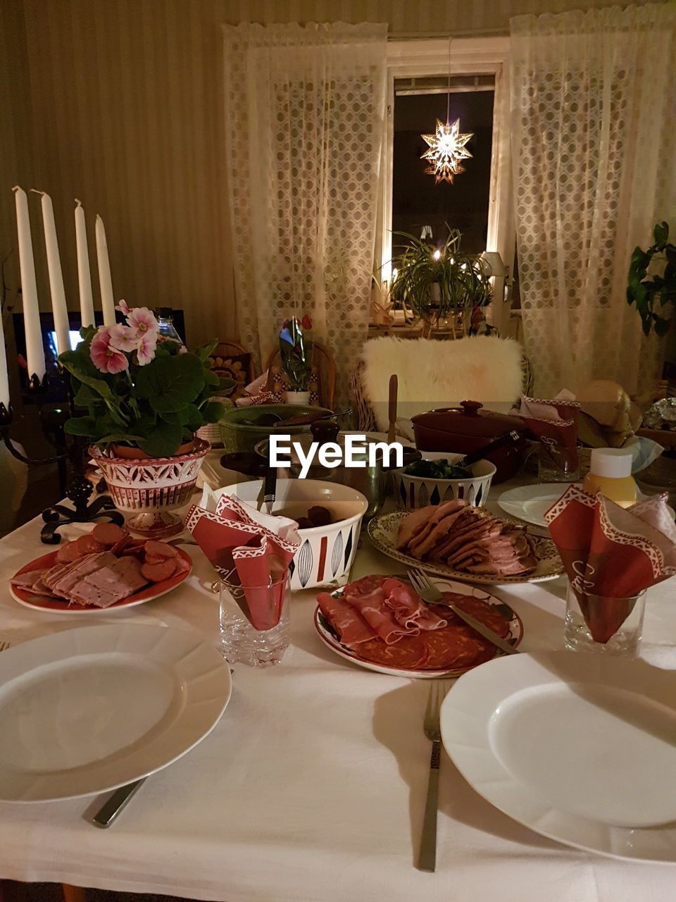 table, indoors, celebration, food and drink, dining table, place setting, plate, chair, tablecloth, no people, food, christmas, home interior, drinking glass, dining room, wineglass, drink, party - social event, christmas decoration, alcohol, illuminated, flower, day, freshness