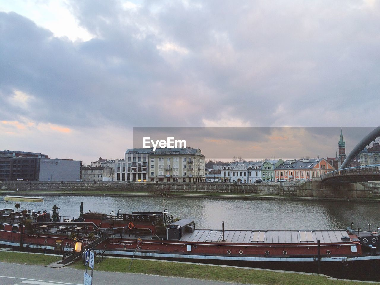 Barge moored on river vistula against cloudy sky