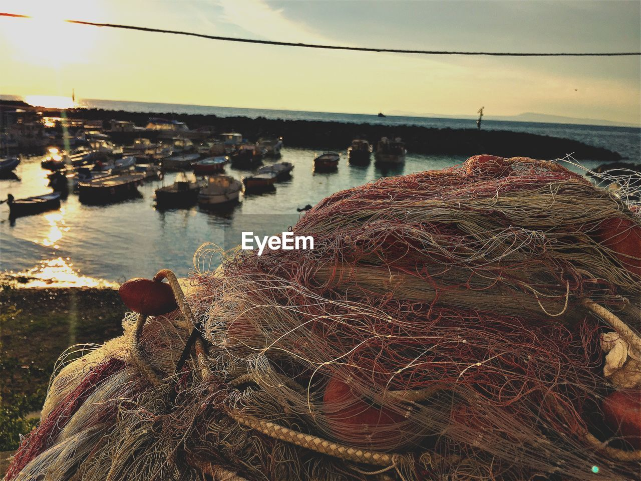 fishing net, fishing industry, rope, sea, water, harbor, fishing equipment, fishing tackle, outdoors, nautical vessel, strength, buoy, sky, nature, no people, sunset, day, close-up