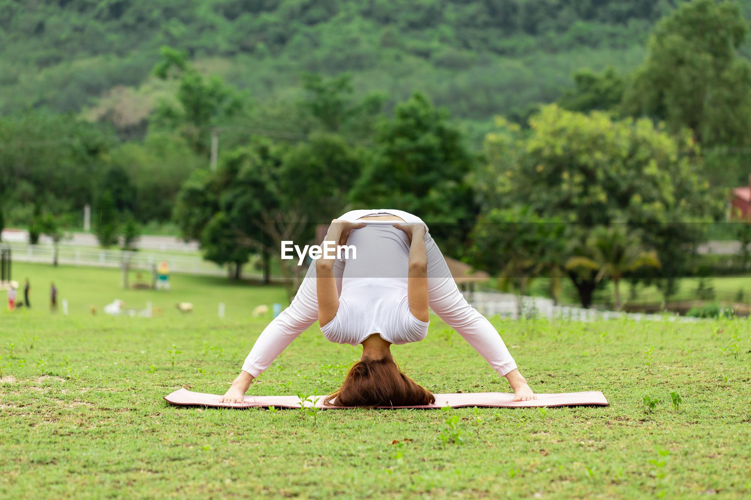 Full length of woman doing yoga on grass