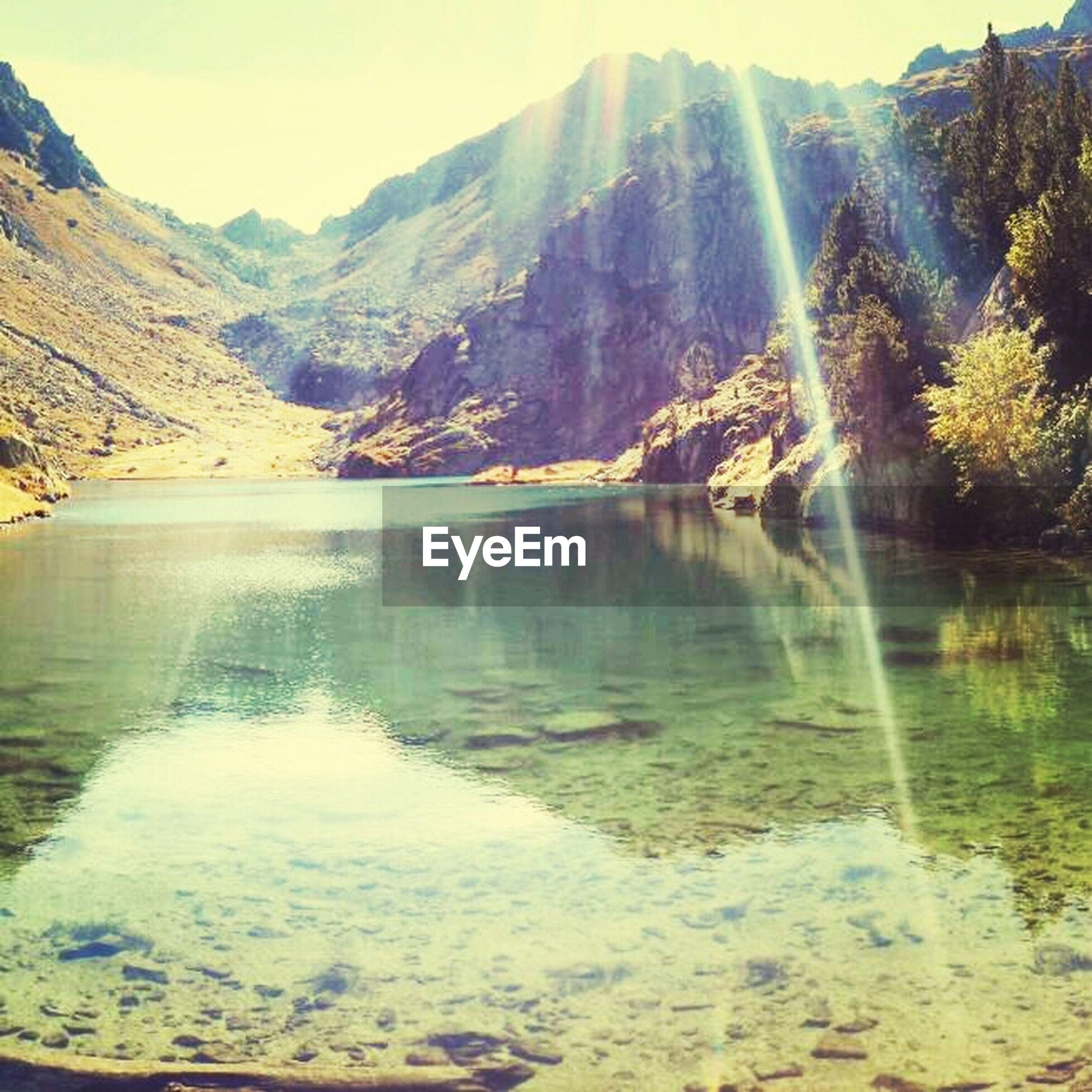 mountain, water, tranquil scene, scenics, tranquility, mountain range, beauty in nature, lake, nature, sunlight, reflection, idyllic, sun, river, non-urban scene, sunbeam, sky, landscape, tree, lens flare