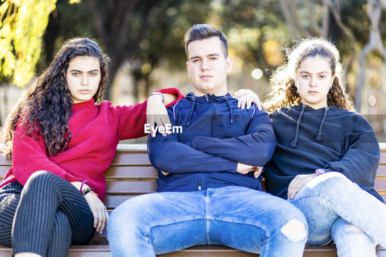 Portrait of teenage friends sitting on seat