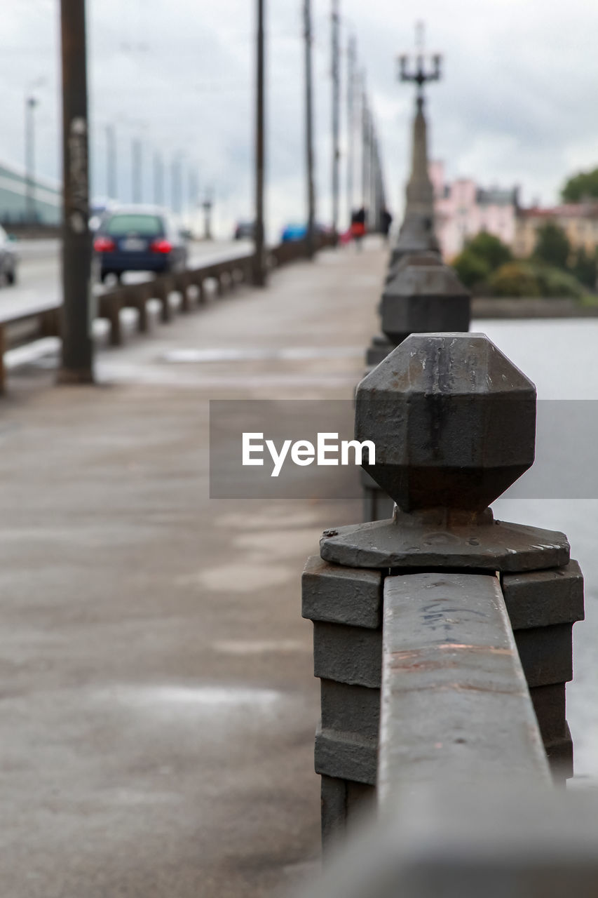 selective focus, in a row, metal, day, no people, focus on foreground, architecture, transportation, close-up, built structure, outdoors, railing, footpath, nature, city, mode of transportation, connection, water, rusty, sky