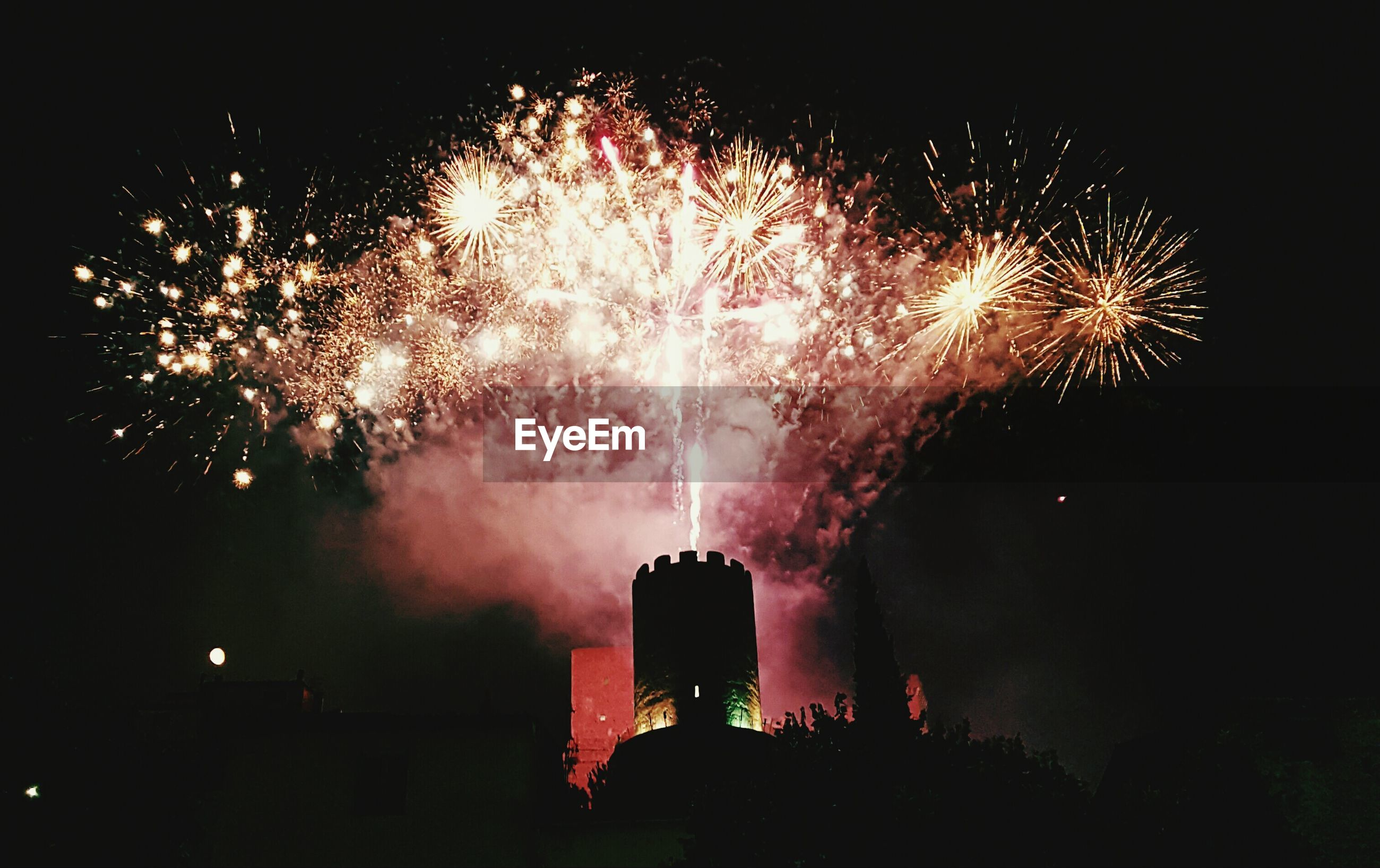 View of buildings with fireworks in sky at night