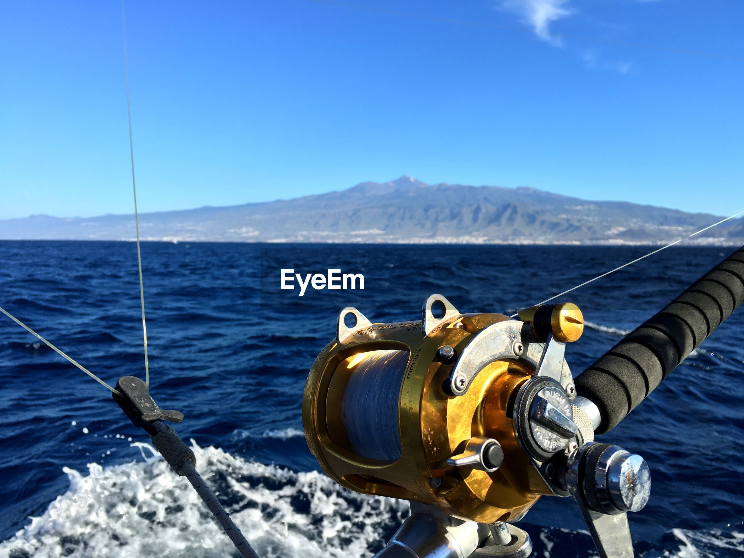 Close-up of fishing rod with sea in background against blue sky