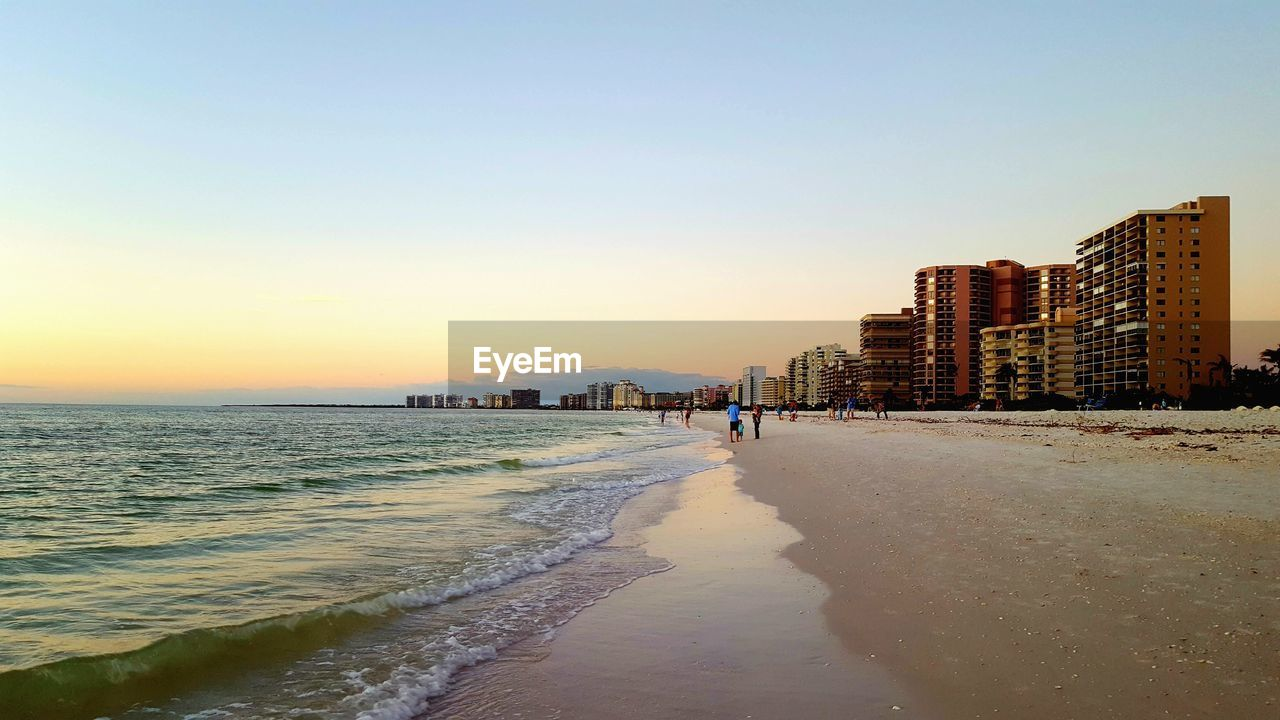 beach, sea, sunset, sand, shore, water, architecture, building exterior, built structure, wave, clear sky, nature, outdoors, vacations, sky, scenics, beauty in nature, horizon over water, travel destinations, real people, city, day