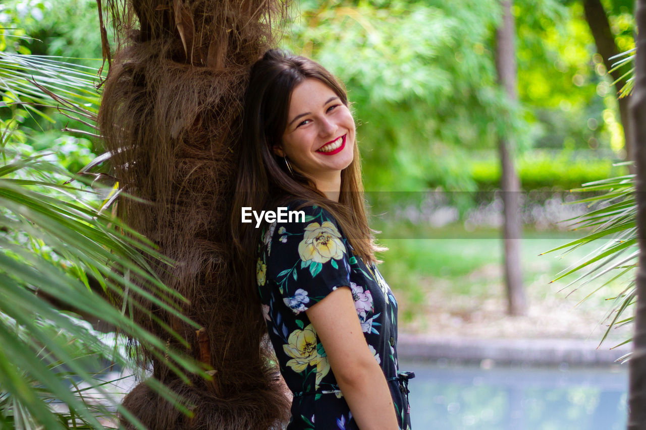 PORTRAIT OF SMILING YOUNG WOMAN AGAINST TREE