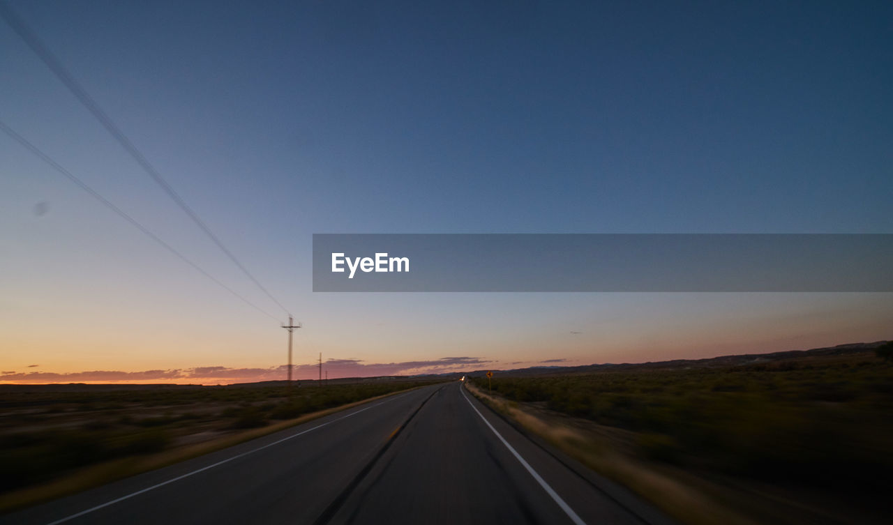 sky, transportation, road, sunset, the way forward, direction, diminishing perspective, nature, copy space, clear sky, no people, beauty in nature, landscape, vanishing point, environment, sign, symbol, tranquil scene, scenics - nature, road marking, outdoors