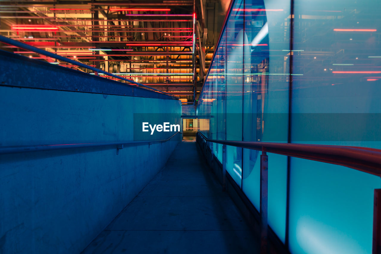 architecture, illuminated, indoors, blue, built structure, industry, no people, the way forward, footpath, railing, factory, direction, metal, building, motion, lighting equipment, pipe - tube, technology, night, ceiling, industrial equipment