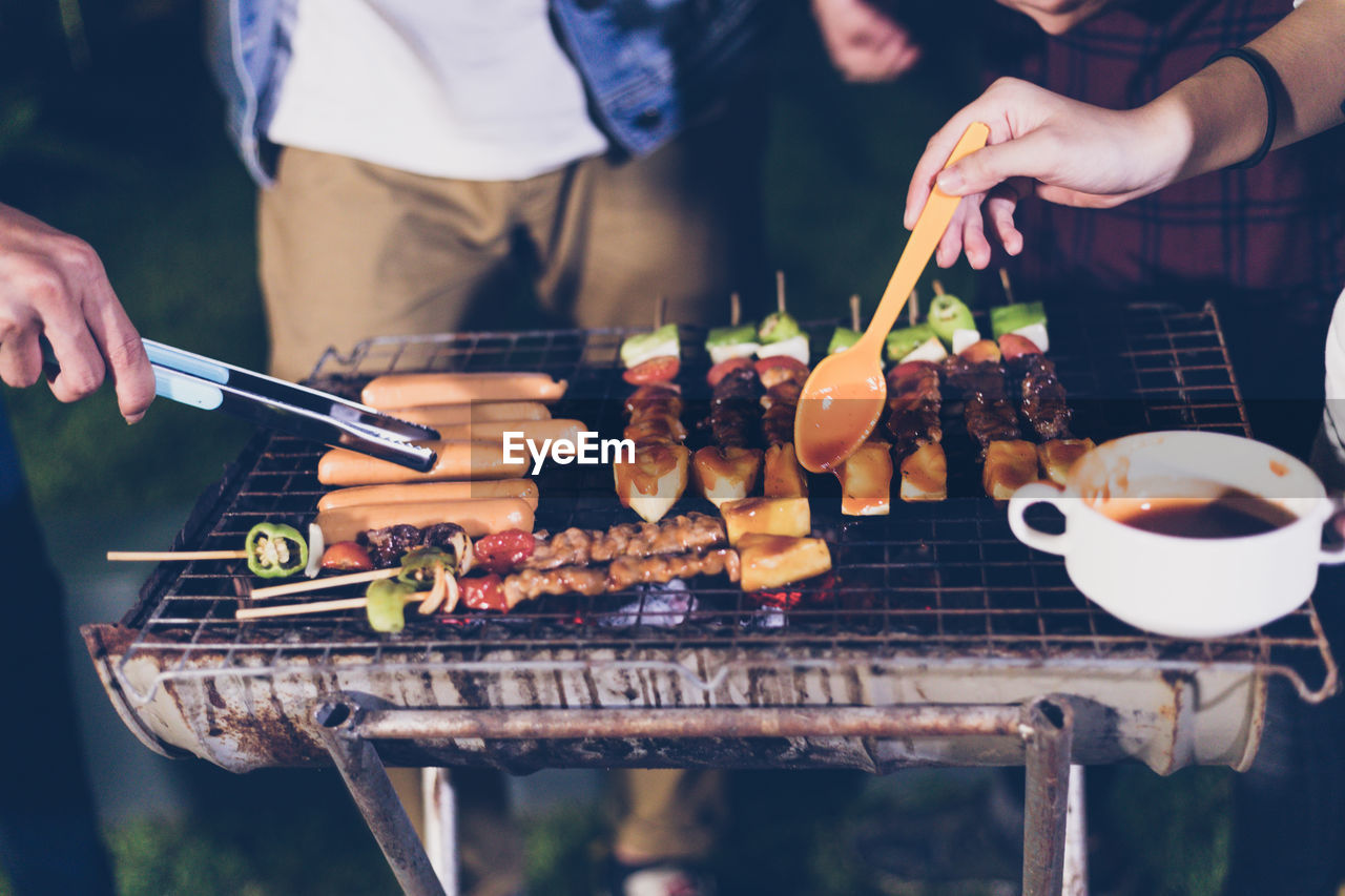 barbecue, food and drink, barbecue grill, skewer, grilled, food, real people, preparation, outdoors, human hand, holding, serving tongs, focus on foreground, freshness, kebab, leisure activity, men, meat, day, togetherness, close-up, people