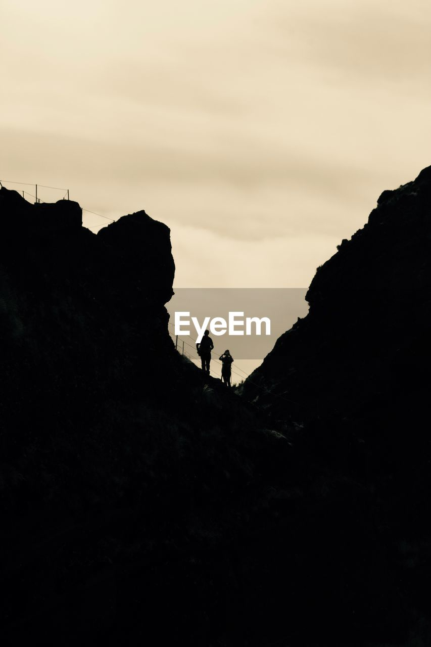 sky, silhouette, leisure activity, real people, rock, nature, beauty in nature, mountain, men, rock - object, lifestyles, two people, standing, activity, scenics - nature, cloud - sky, tranquil scene, people, tranquility, adventure, outdoors