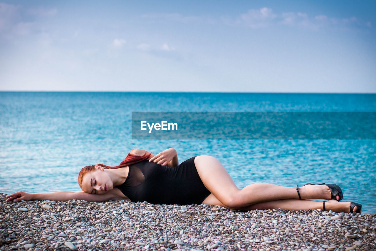 Full Length Of Sensuous Woman In Swimwear Lying Down At Beach