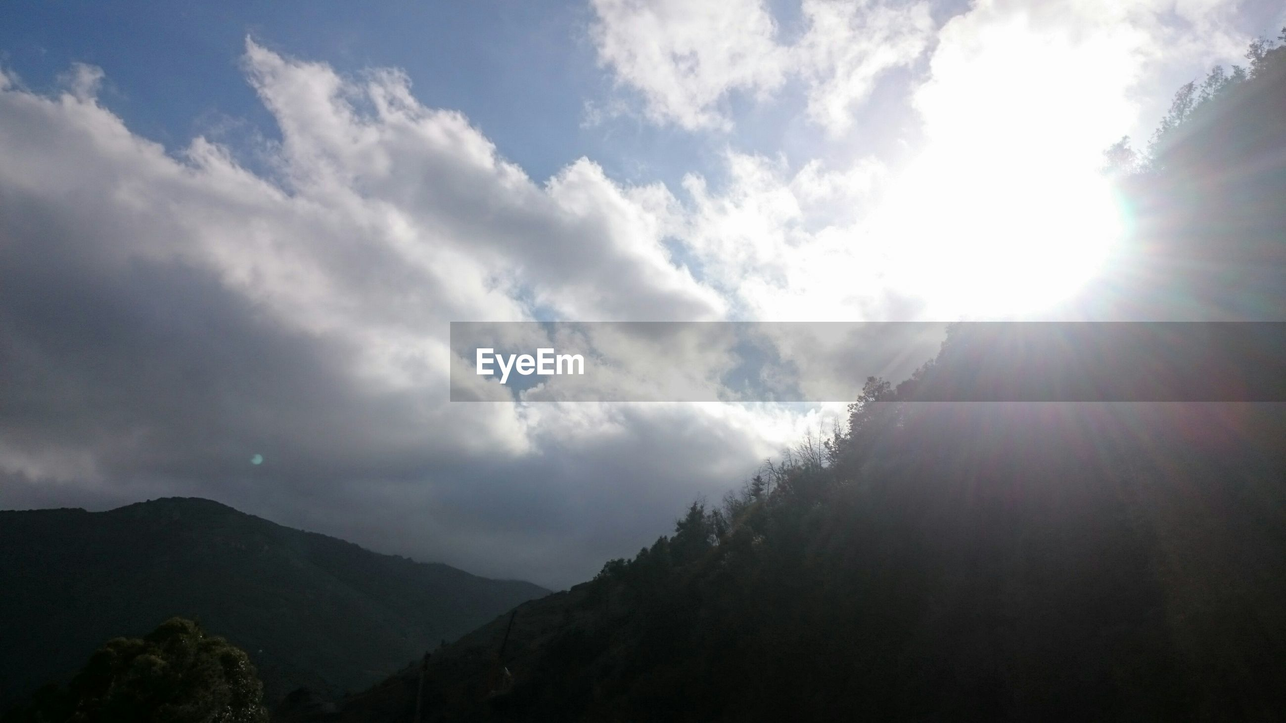 mountain, tranquil scene, tranquility, sun, scenics, sky, beauty in nature, sunbeam, sunlight, nature, mountain range, cloud - sky, landscape, lens flare, idyllic, cloud, silhouette, non-urban scene, tree, outdoors