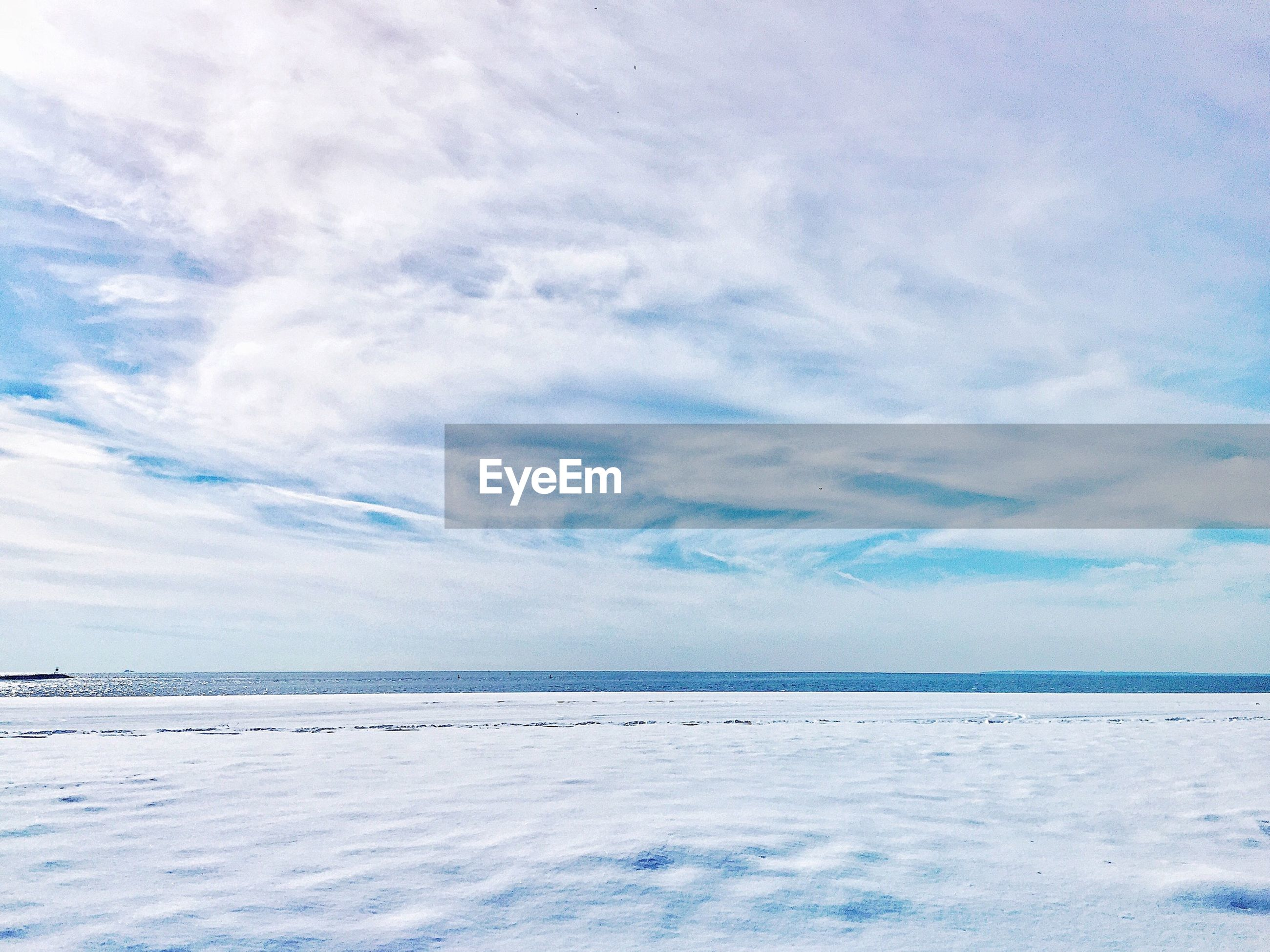 Scenic view of snow and sea against cloudy sky