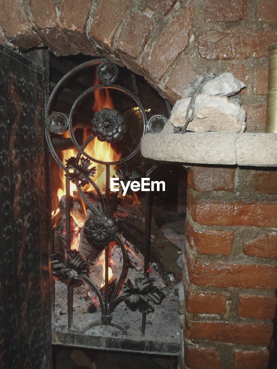 wall, no people, wall - building feature, brick, close-up, brick wall, built structure, burning, hanging, fire, architecture, day, metal, outdoors, nature, fire - natural phenomenon, fireplace, heat - temperature, lighting equipment, illuminated, stone wall, electric lamp