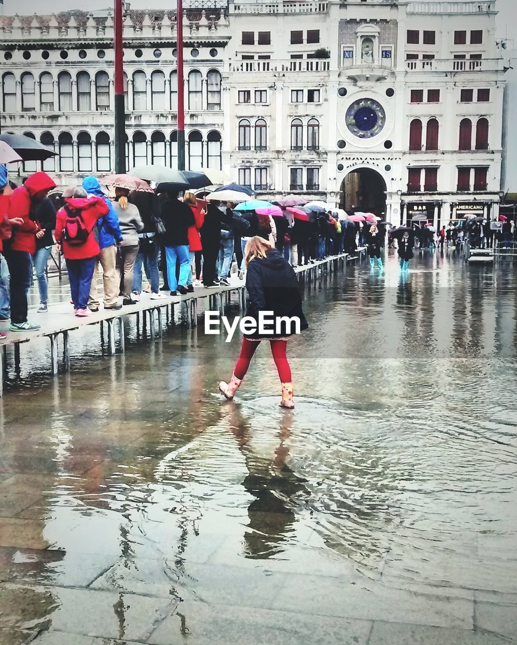 architecture, built structure, building exterior, water, rain, full length, wet, real people, large group of people, walking, women, day, flood, city life, men, outdoors, leisure activity, city, lifestyles, puddle, sky, adult, people