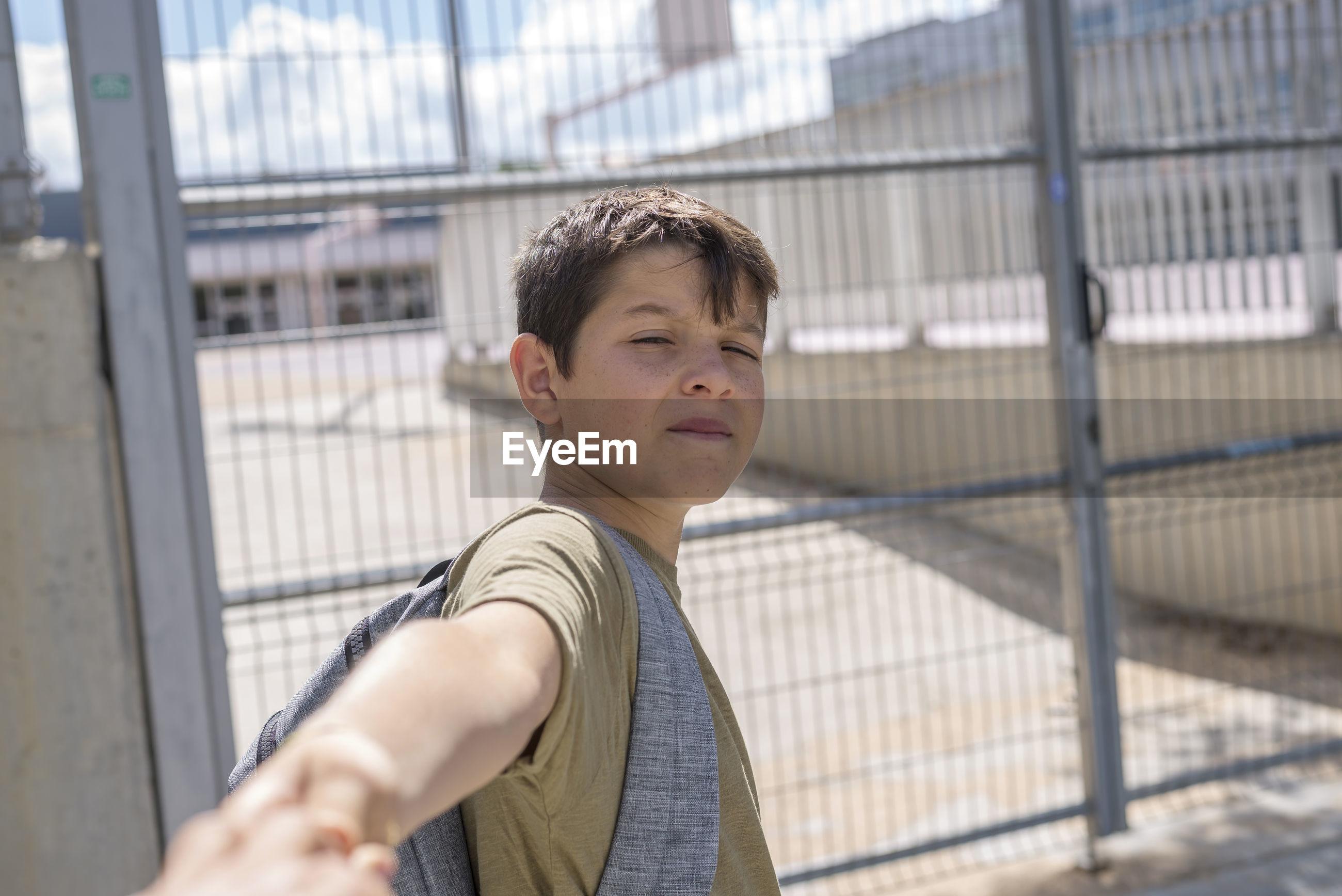 Portrait of boy against gate
