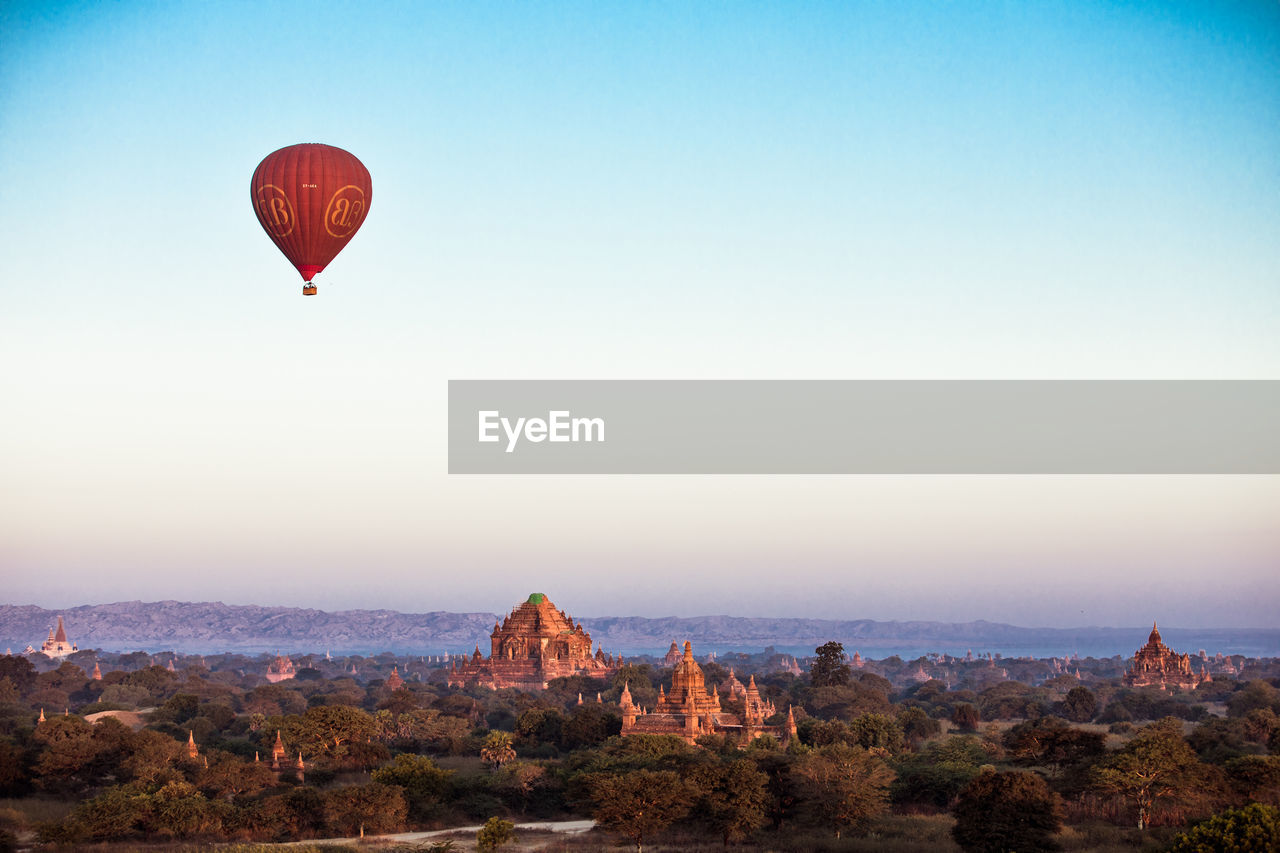 sky, balloon, hot air balloon, nature, scenics - nature, mid-air, adventure, landscape, air vehicle, beauty in nature, travel, travel destinations, clear sky, no people, rock formation, tranquility, rock, flying, tranquil scene, red