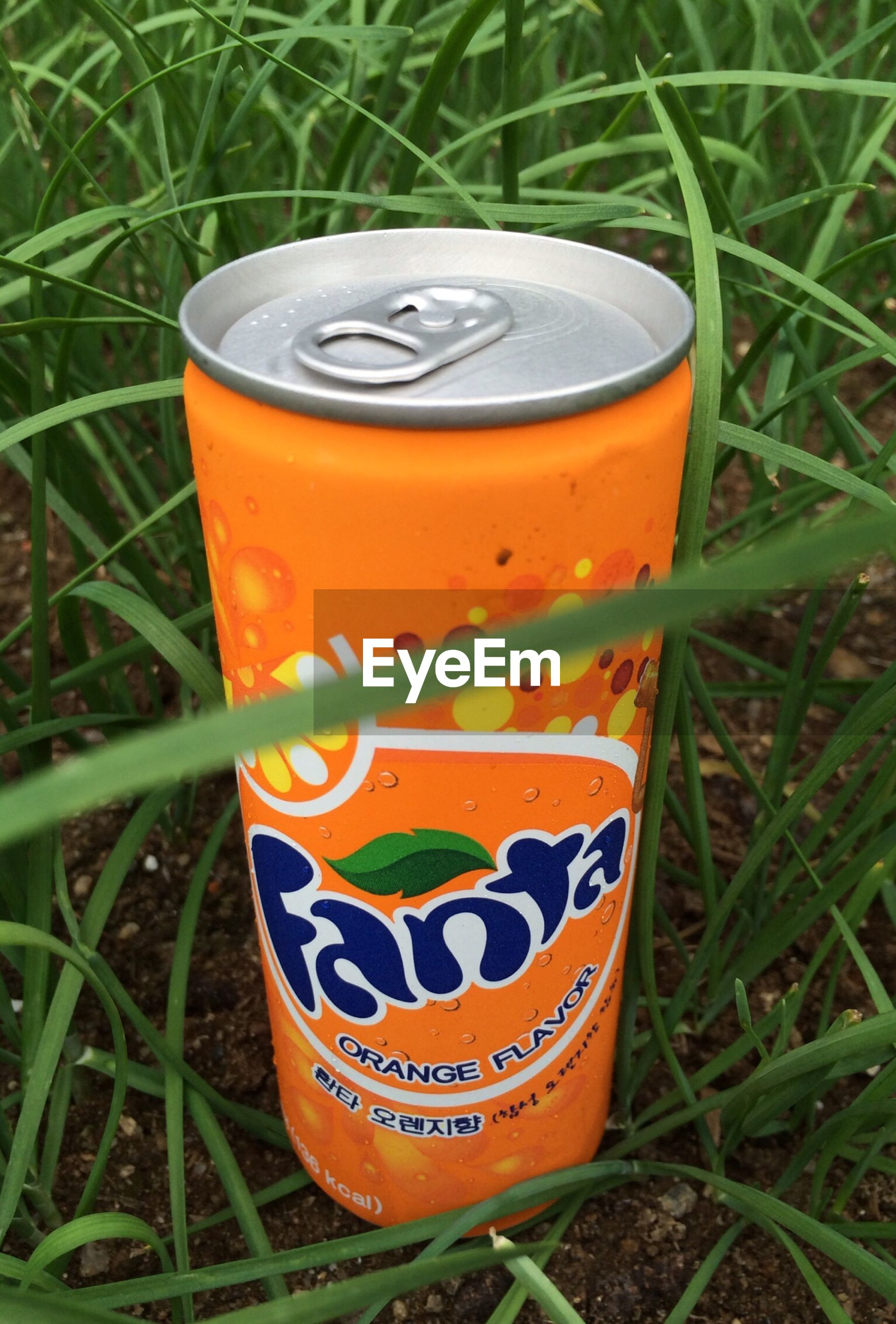 text, communication, western script, grass, drink, close-up, yellow, food and drink, field, red, number, no people, warning sign, orange color, refreshment, outdoors, day, freshness, still life, metal