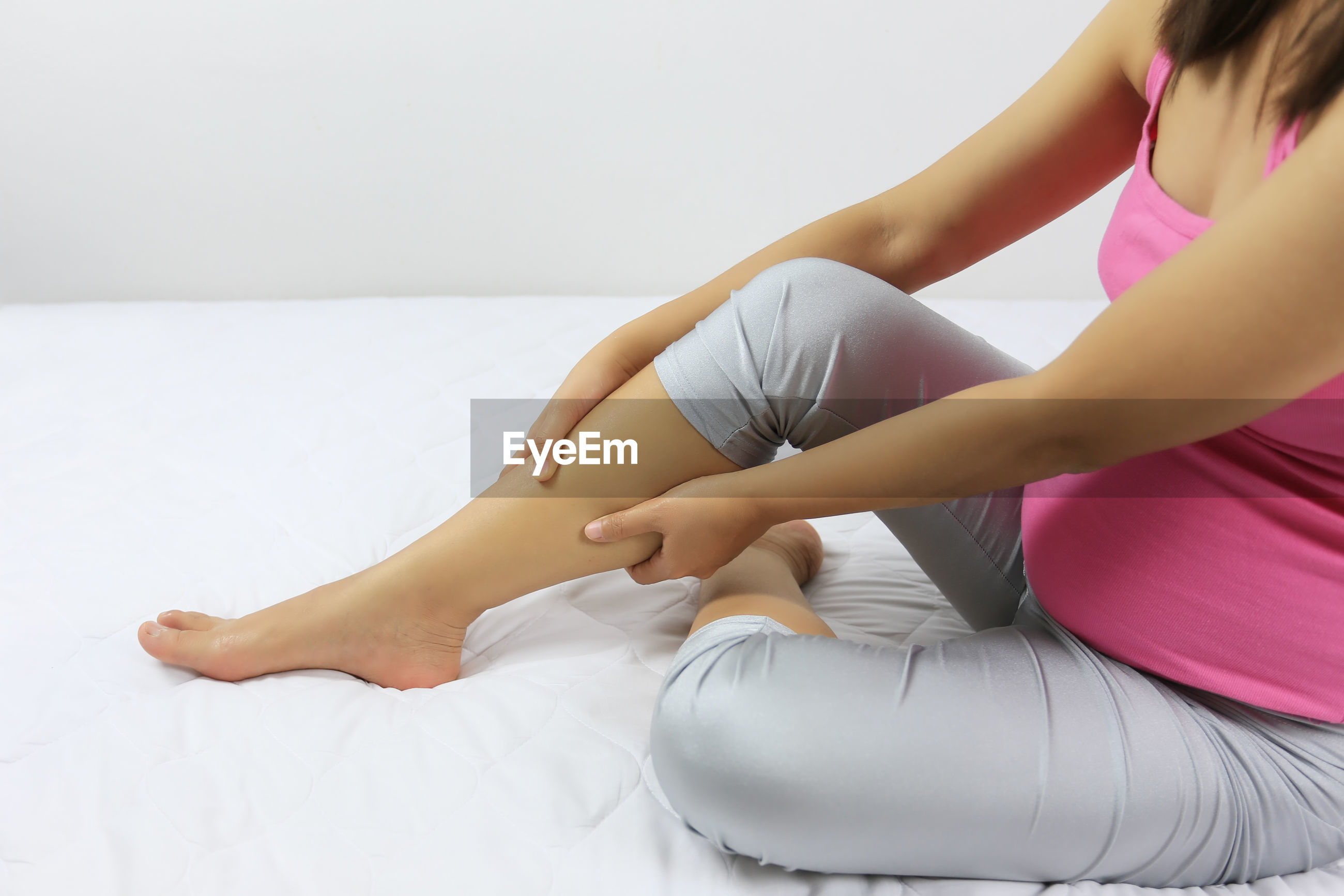 Low section of pregnant woman massaging leg while sitting on bed