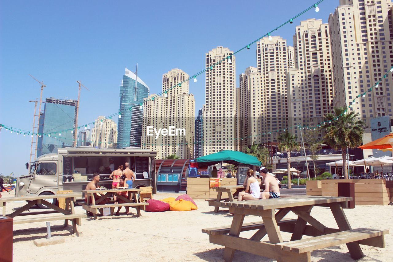 People Relaxing At Open Restaurant By Cityscape Against Clear Sky