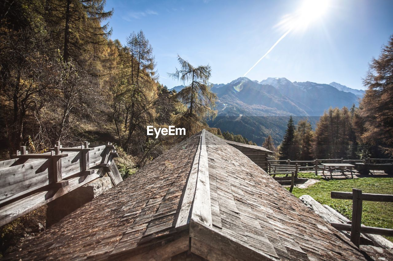 mountain, wood - material, nature, sky, sunlight, day, plant, tree, tranquility, no people, beauty in nature, built structure, tranquil scene, architecture, scenics - nature, environment, landscape, land, non-urban scene, mountain range, outdoors