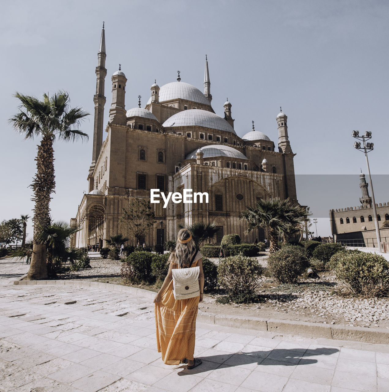 Rear view of woman standing against castle during sunny day