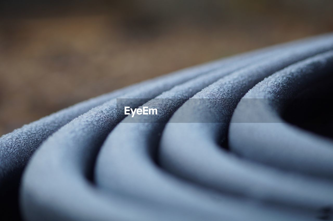 selective focus, close-up, no people, towel, blue, indoors, textile, black color, still life, day, pattern, focus on foreground, strength, protection, rolled up, shape, design, metal, white color