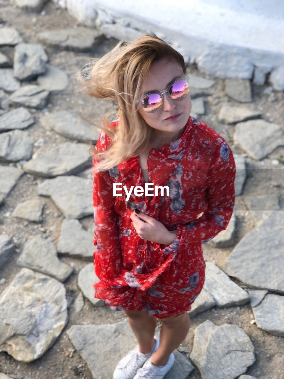 Young Woman Wearing Sunglasses Standing On Rock