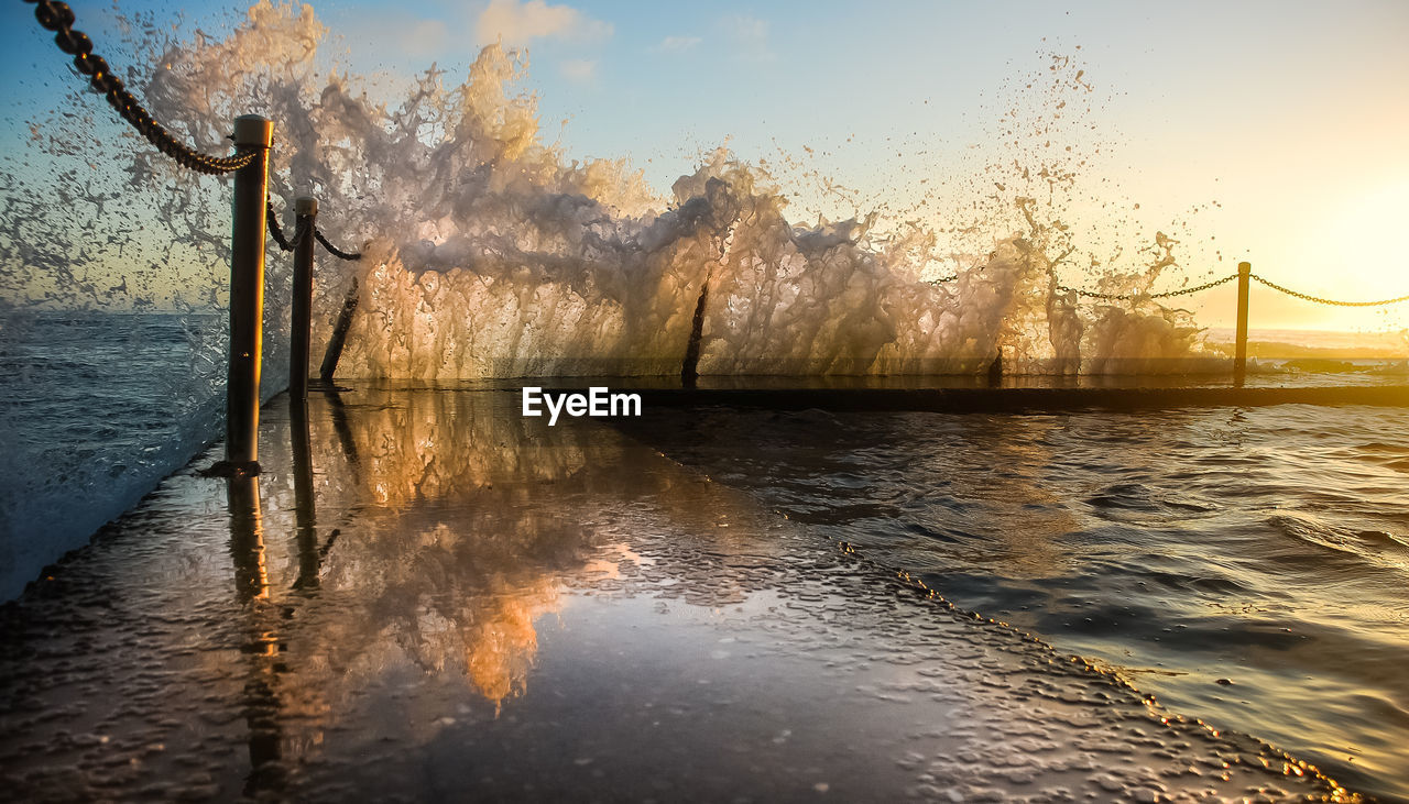 water, sky, reflection, nature, sunset, beauty in nature, scenics - nature, waterfront, no people, motion, tranquility, tranquil scene, architecture, outdoors, built structure, sunlight, river, non-urban scene, splashing, flowing water, power in nature