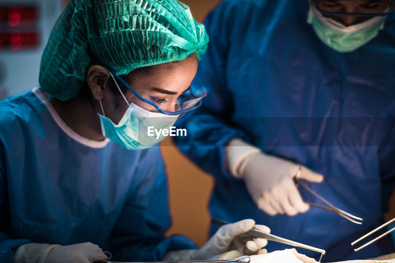 doctor, hospital, occupation, surgery, two people, surgeon, surgical mask, expertise, operating room, healthcare and medicine, indoors, working, professional occupation, looking, concentration, scrubs, adult, people, surgical cap, equipment, healthcare worker, care, skill, surgical equipment, operating gown, medical procedure