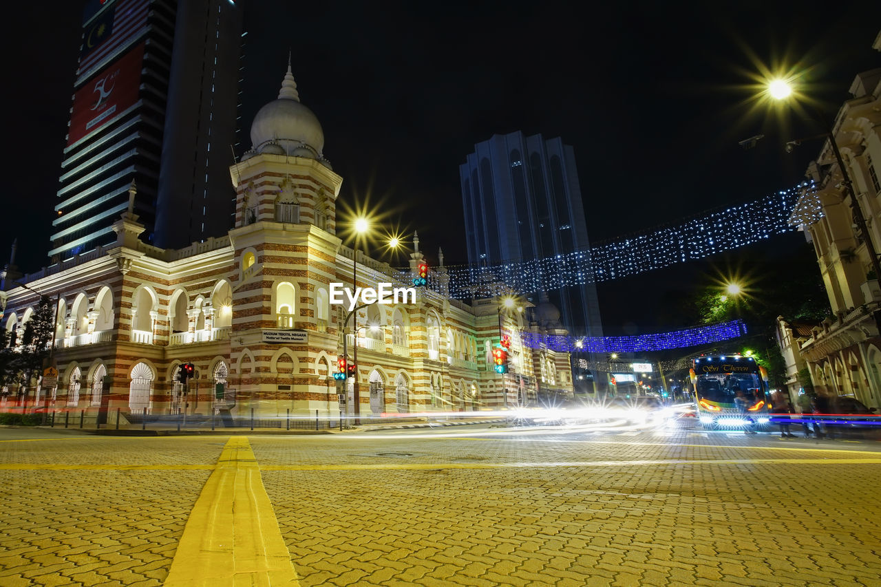 LIGHT TRAILS ON ROAD AGAINST BUILDINGS