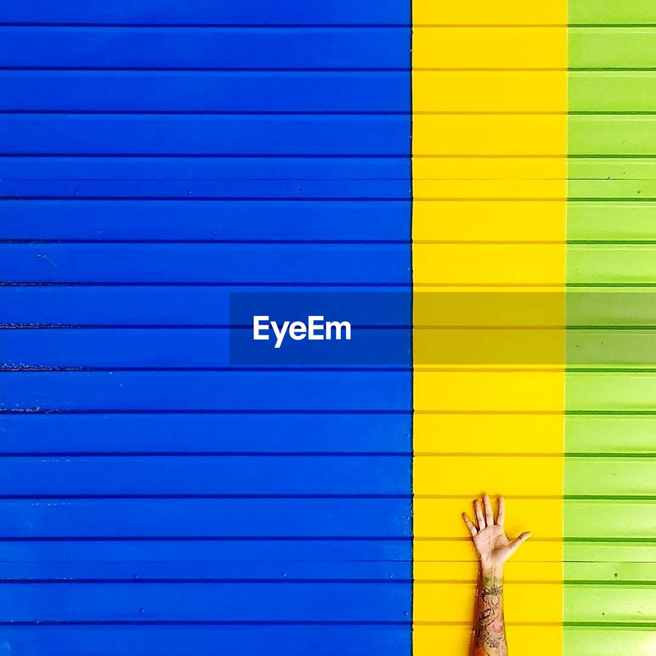 human body part, yellow, blue, human hand, corrugated iron, multi colored, green color, real people, day, outdoors, close-up, people
