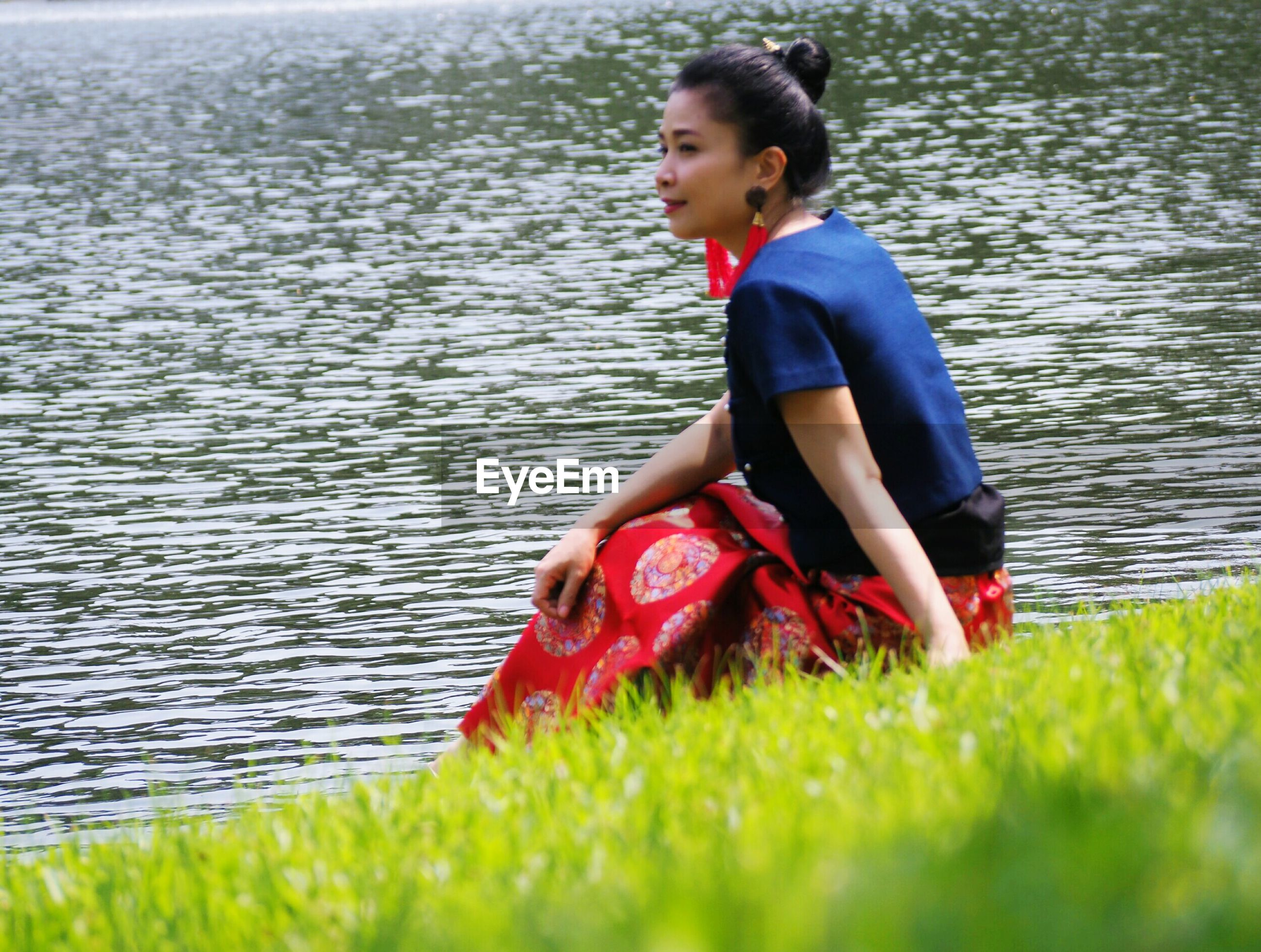 Side view of young woman sitting by lake