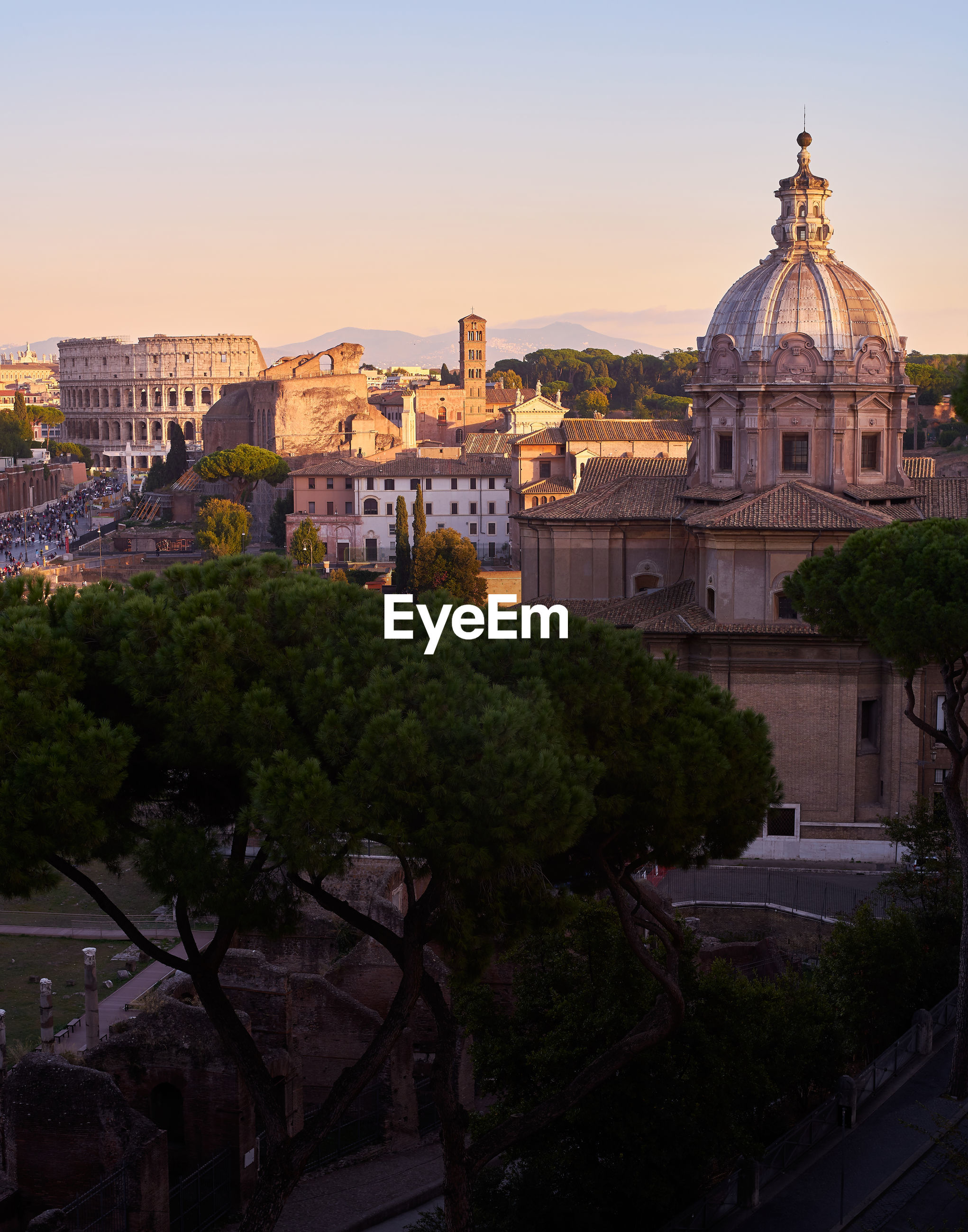 Buildings in city against sky during sunset, coloseum