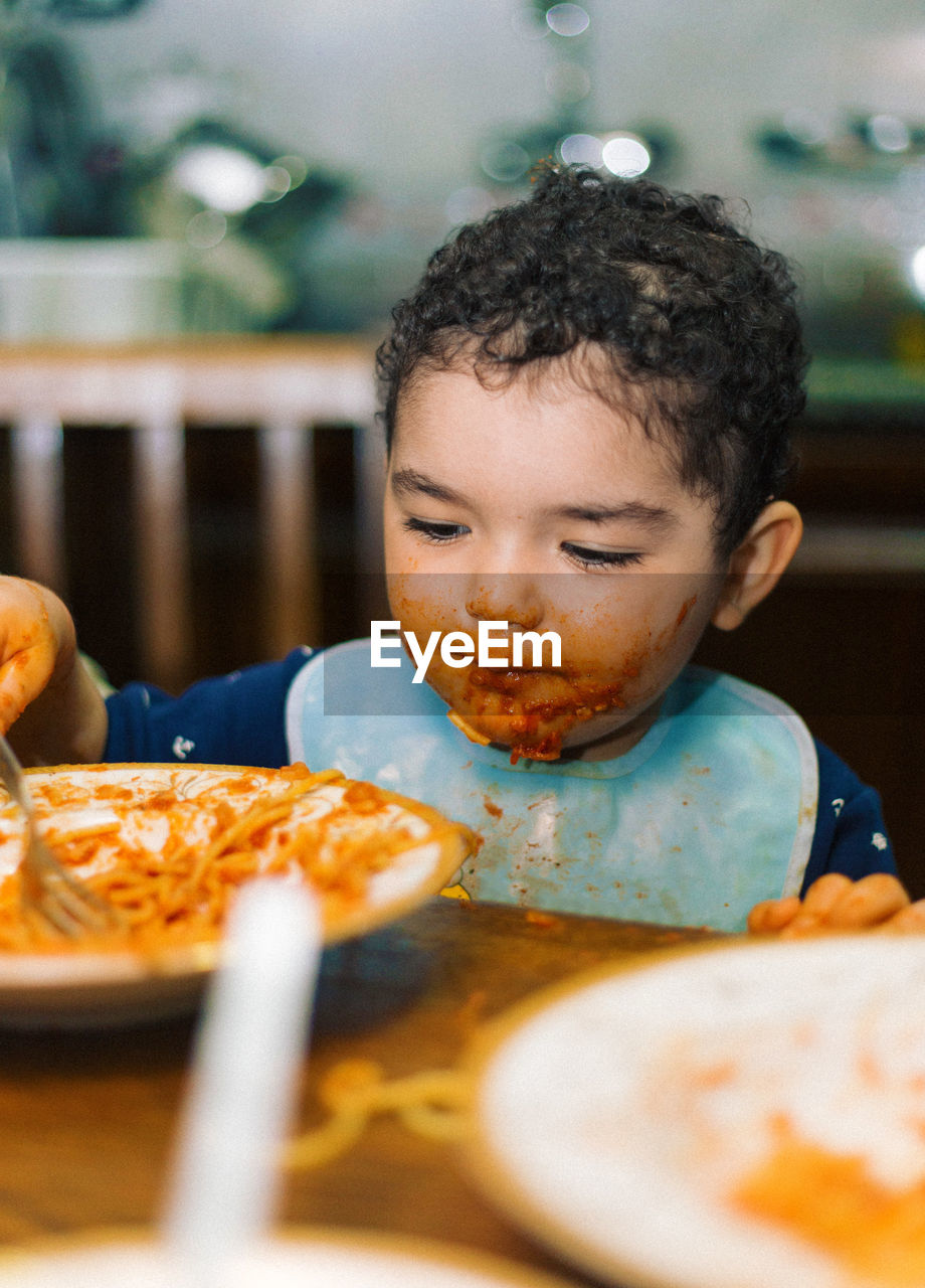 Boy Having Food On Table At Home