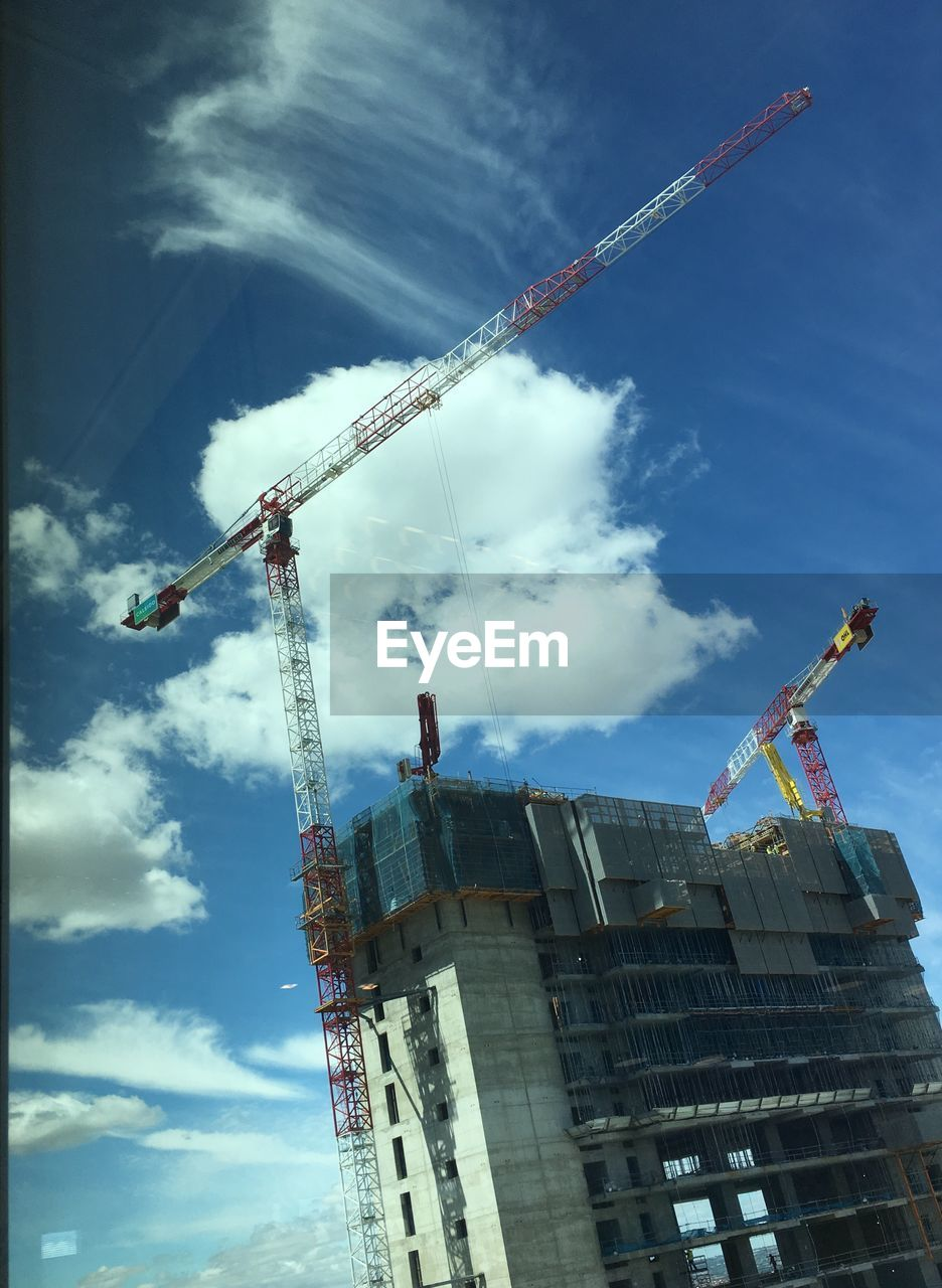 construction industry, crane - construction machinery, machinery, architecture, built structure, industry, construction site, low angle view, sky, development, cloud - sky, building exterior, nature, incomplete, building, day, construction equipment, no people, crane, outdoors