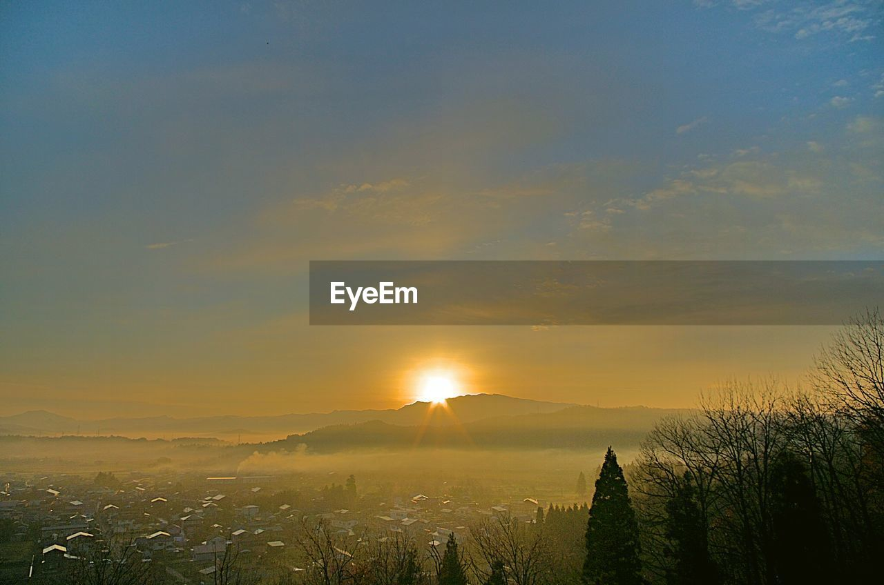 sunset, scenics, beauty in nature, sky, mountain, tranquil scene, growth, no people, tranquility, nature, sun, landscape, outdoors, city, tree, architecture, cityscape, day