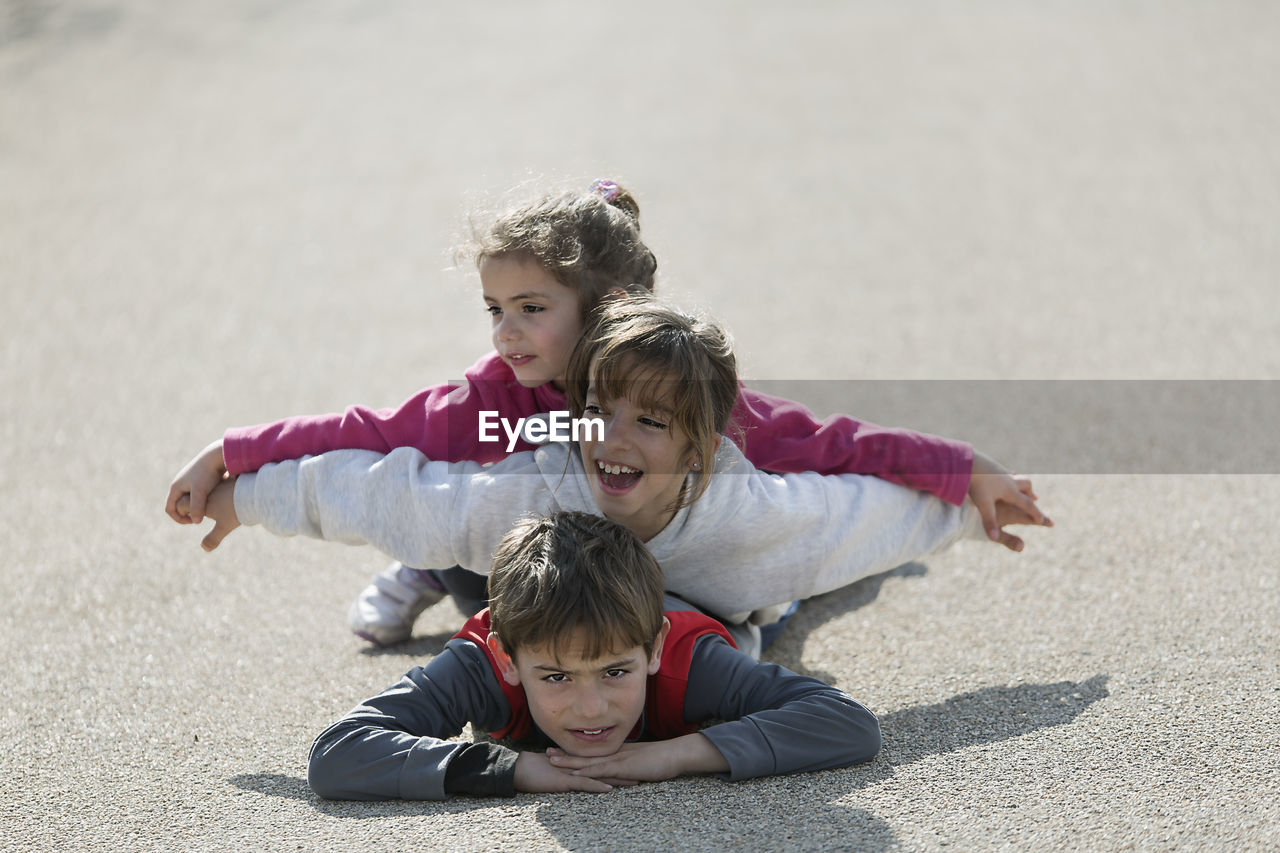 Portrait Of Boy With Sisters Lying Down On Road