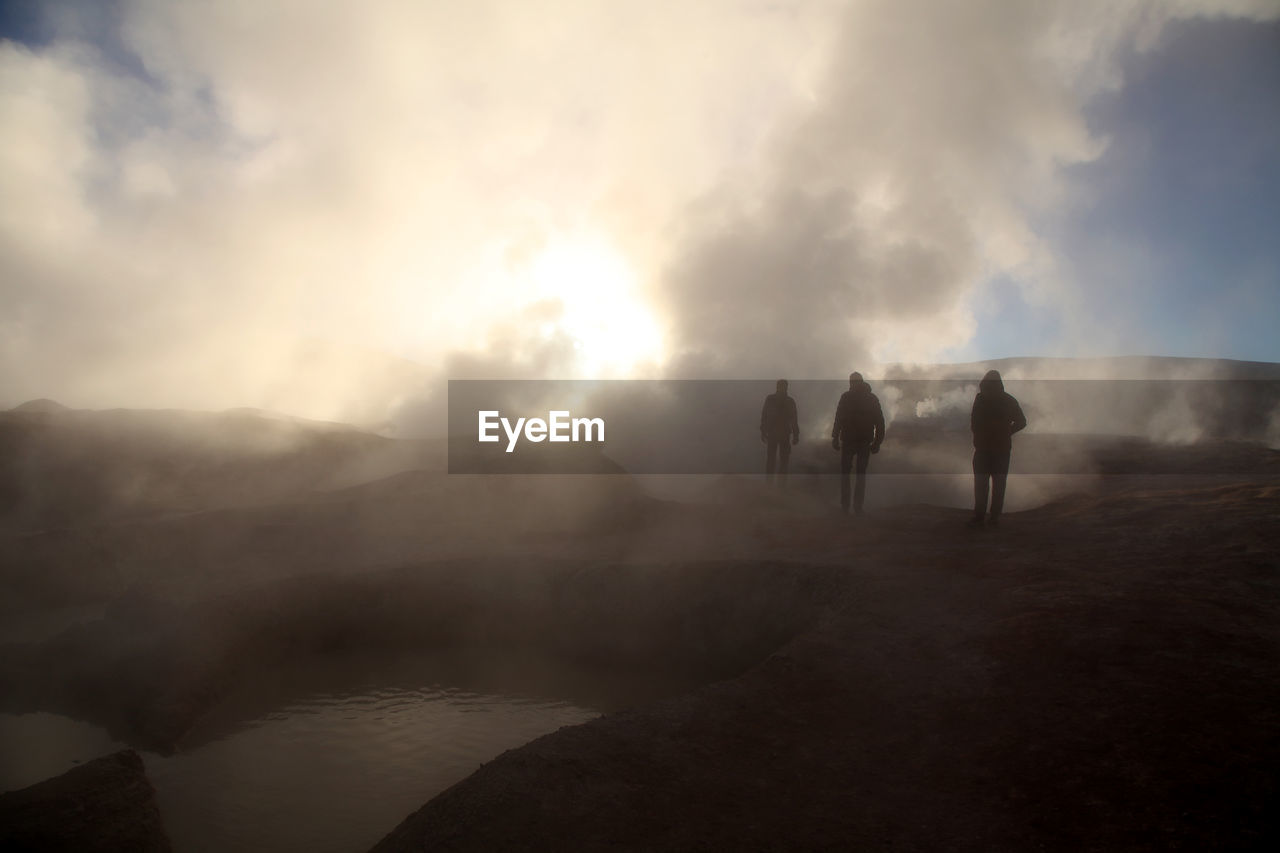 Tourists Watching Steam Rising From Geyser At Salar De Uyuni